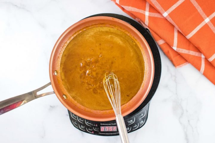 Overhead shot of a small orange skillet of brown gravy over a warming unit on a white marble counter.There is a whisk in the skillet, and an orange napkin with white stripes on the counter at the top right of the picture.