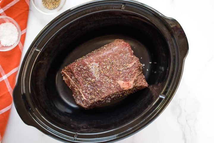 Uncooked beef roast in a slow cooker on a white marble counter. On the left side of the photo is an orange napkin with white stripes. On the napkin is a small glass bowl with salt. Next to the napkin is small glass bowl with pepper.