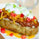 Baked potato topped with chili, shredded cheddar cheese, diced tomatoes, sour cream, and diced green onions, with shredded cheese and diced tomatoes are on the counter around the potato.