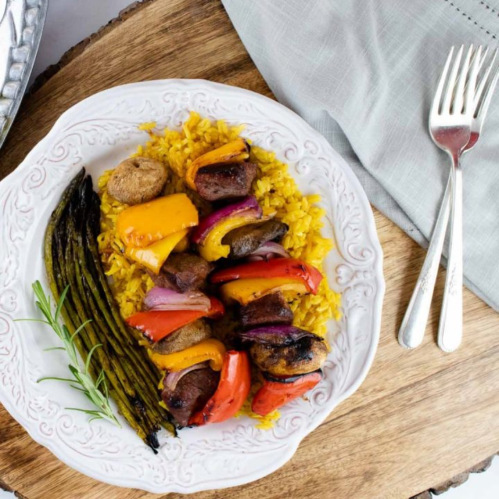 plate of cooked beef and vegetable kabobs over yellow rice served with grilled asparagus