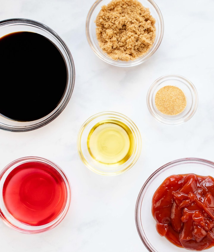 overhead shot of bowls with red wine vinegar, woy sauce, brown sugar, oil, garlic salt, and ketchup
