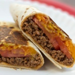 A burrito with ground beef, tomato slices, and melted cheese, cut in half on a white plate.