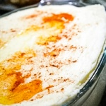 Glass dish with mashed potatoes topped with butter and paprika
