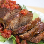 Sliced pot roast on a white plate and a bed of lettuce, garnished with diced tomatoes.
