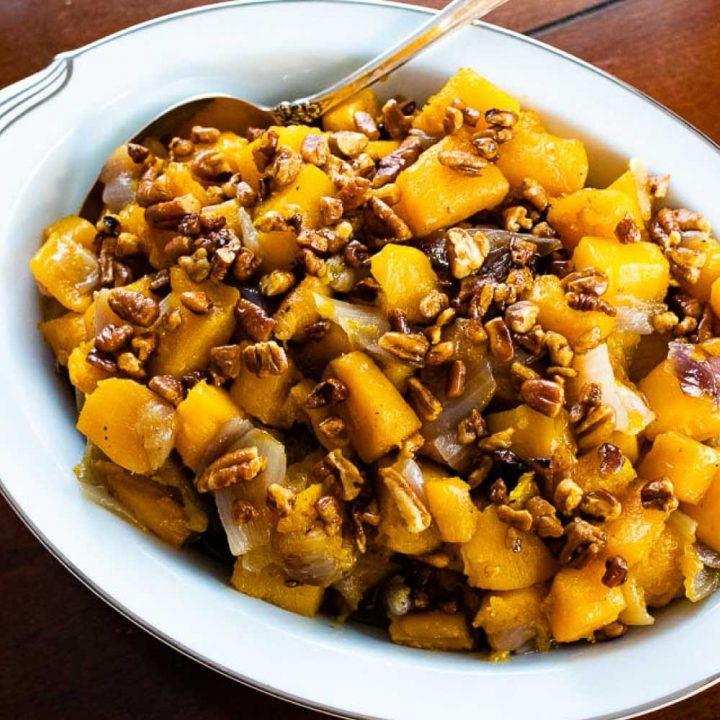 a bowl of roasted butternut squash with candied pecans and text roasted butternut squash with candied pecans