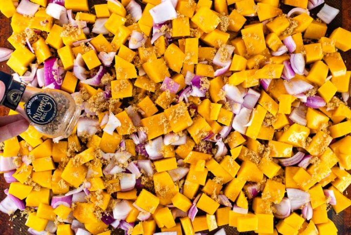 Sheet pan with cubed butternut squash and diced onion spread out and sprinkled with brown sugar; a jar with pieces of nutmeg is displayed above the pan