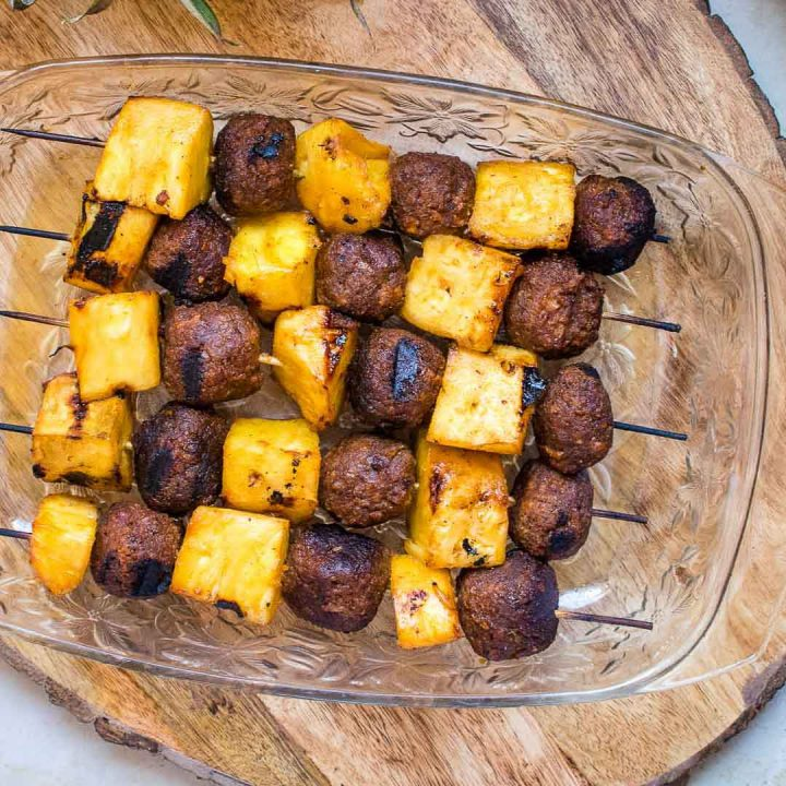 Glass dish with grilled vegetarian meatball and pineapple kabobs on a cutting board with whole pineapple to the side