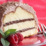 pound cake with layers of chocolate hazelnut cream frosted with chocolate cool whip frosting on a plate garnished with raspberries