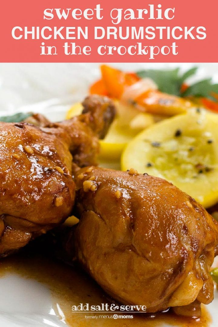 Two chicken drumsticks on a white plate with sliced yellow squash, onions, and bell peppers. Text Sweet Garlic Chicken Drumsticks in the Crockpot Add Salt & Serve formerly Menus4Moms