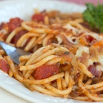 Baked spaghetti on white plate with a fork