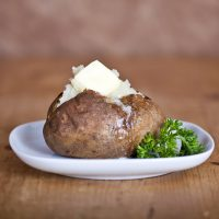 Baked Potato with butter garnished with parsley on a white plate
