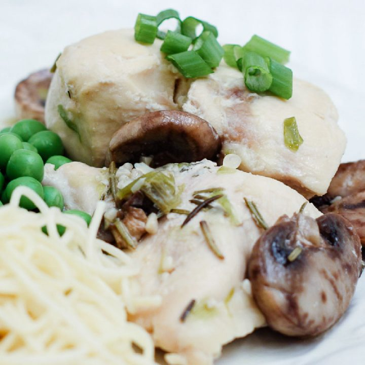 Chicken, mushrooms, green peas, and angel hair pasta on a white plate garnished with diced green onions.