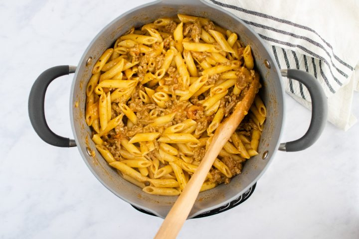 overhead view of cooked penne pasta and cooked ground beef in a creamy sauce in a large pot