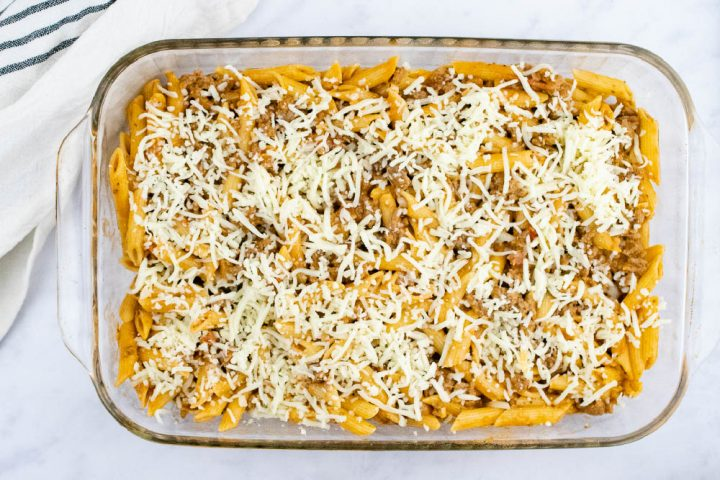 Overhead view of unbaked penne pasta bake topped with shredded cheese in a glass pan