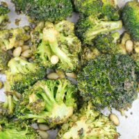 Overhead view of roasted broccoli with pine nuts