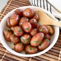 Boiled red potatoes buttered and garnished with parsley in a white bowl with a wooden spoon