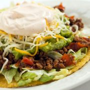 A plate with beef tostados made with guacamole, shredded cheese, and sour cream.