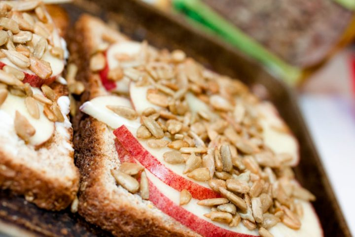 Image of toast spread with mayo, apple slices, and sunflower seeds and text Add Salt & Serve