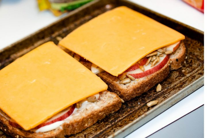 Image of Open-faced Apple Cheddar Melt Sandwich with bread, mayo, apple slices, sunflower seeds, and cheddar and text Add Salt & Serve