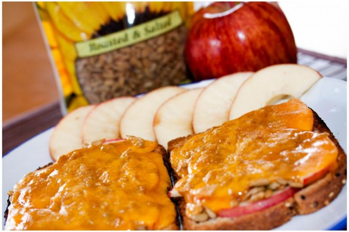 Image of Open-faced Apple Cheddar Melt Sandwich with bread, mayo, apple slices, sunflower seeds, and cheddar melted on top and text Apple Cheddar Melt: Add Salt & Serve